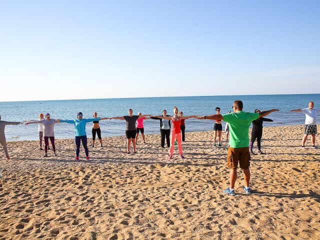 Разминка на пляже под руководством тренера
